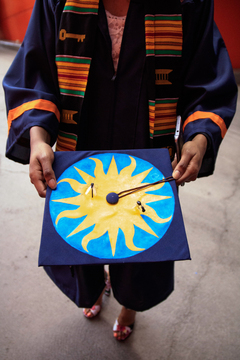 A student shows off her hand decorated graduation cap.